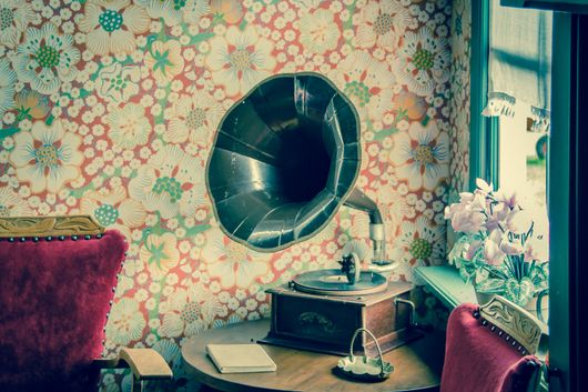antique vinyl record player next to vintage chairs